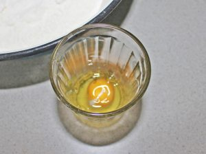 В стакан разбиваем одно яйцо