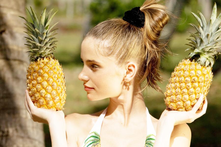 девушка держит ананасы